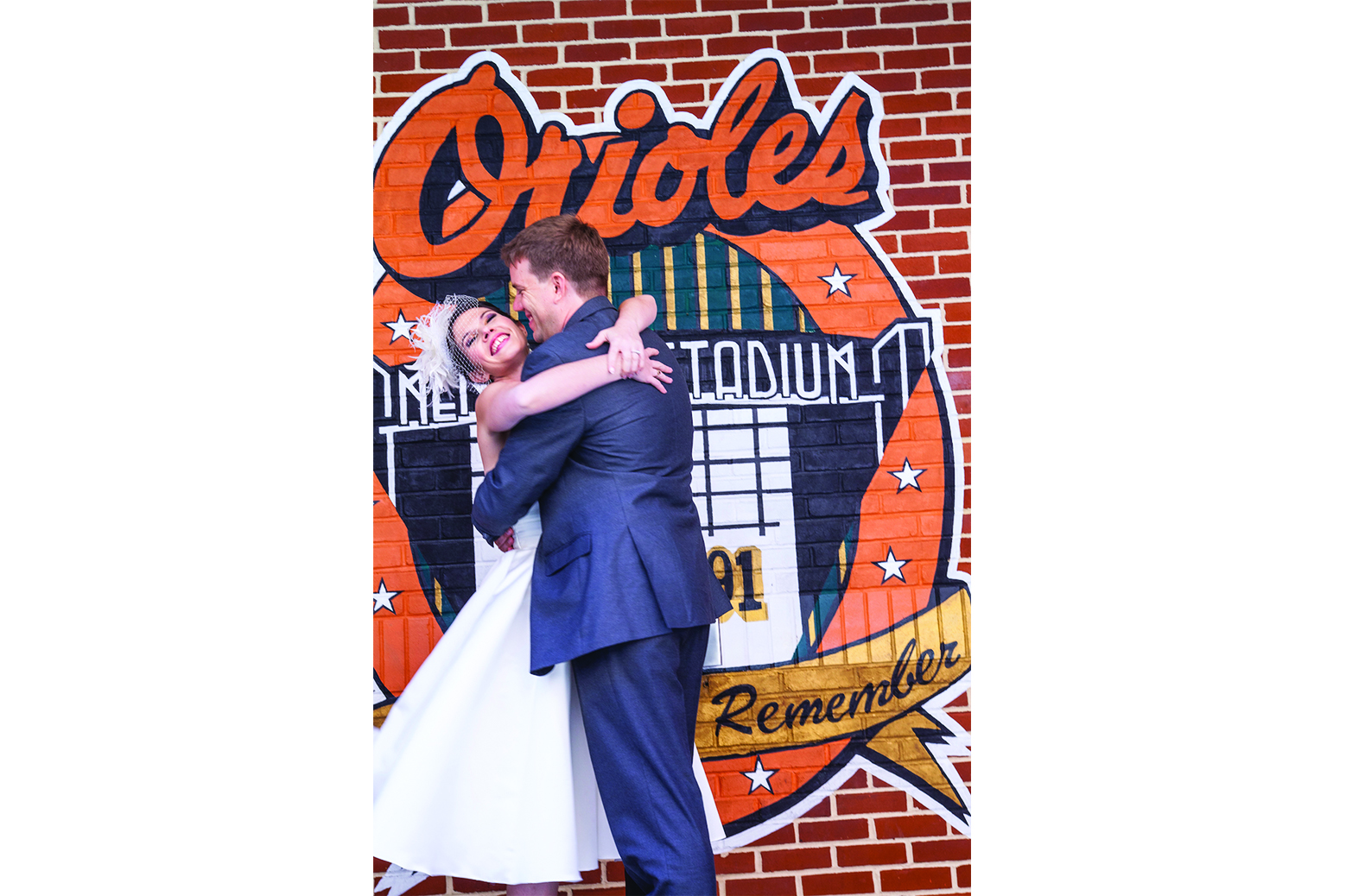 Bride and groom in front of Orioles wall