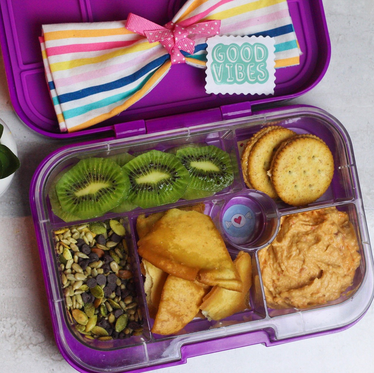 Pick your child's favs & create a trail mix! - Sea salt pita chips, hummus, trail mix (pepitas, sunflower seeds, & chocolate chips), kiwi, and whole wheat peanut butter crackers!