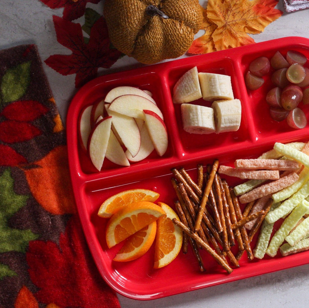 busy toddlers at home? make a snack tray to help keep them out of the kitchen! i find this super helpful. - Oranges, pretzel sticks, veggie straws, grapes, banana slices, and apples!