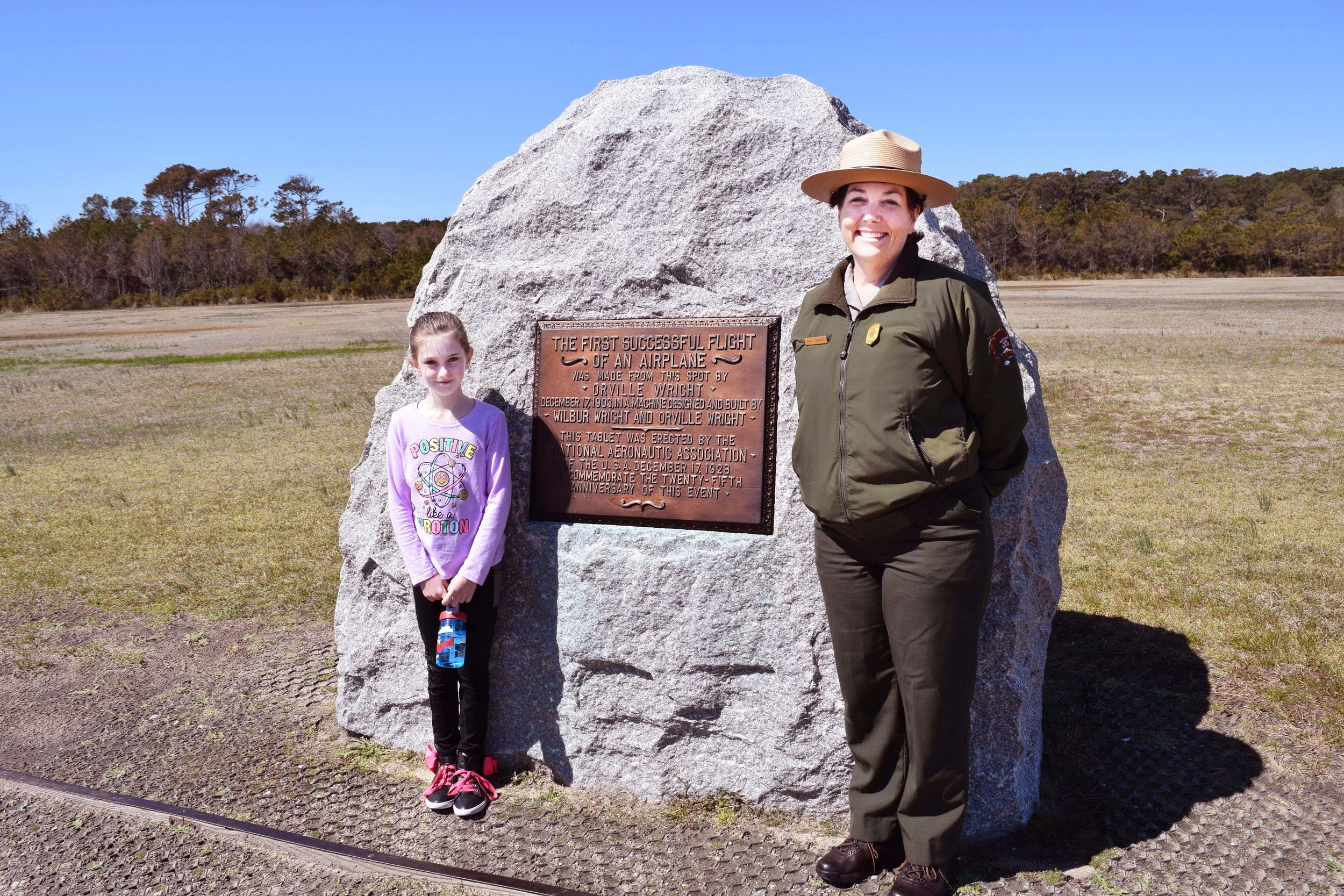 Molly Lam, 10, left, of Abilene, Texas poses with park ranger Amiee Ginnever at the lift-off monument at Wright Brothers National Memorial.