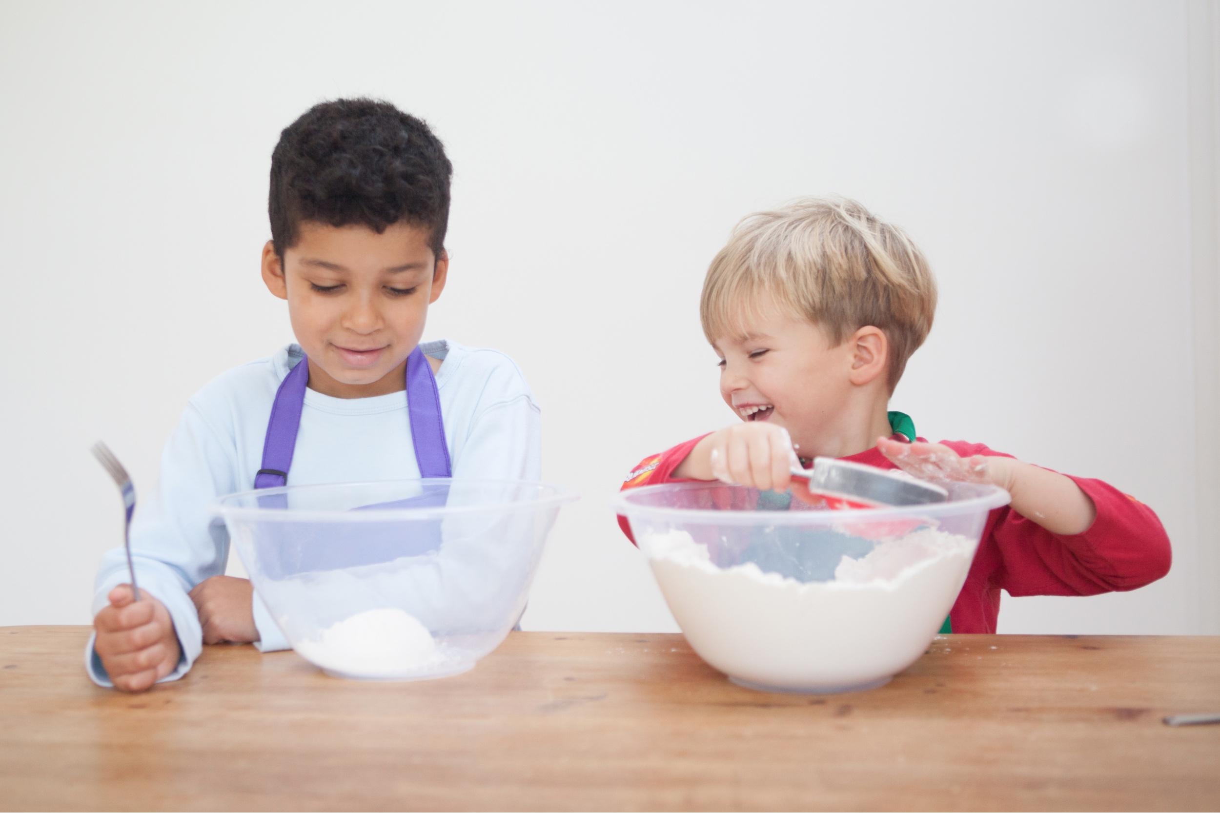 Two boys having fun measuring ingredients