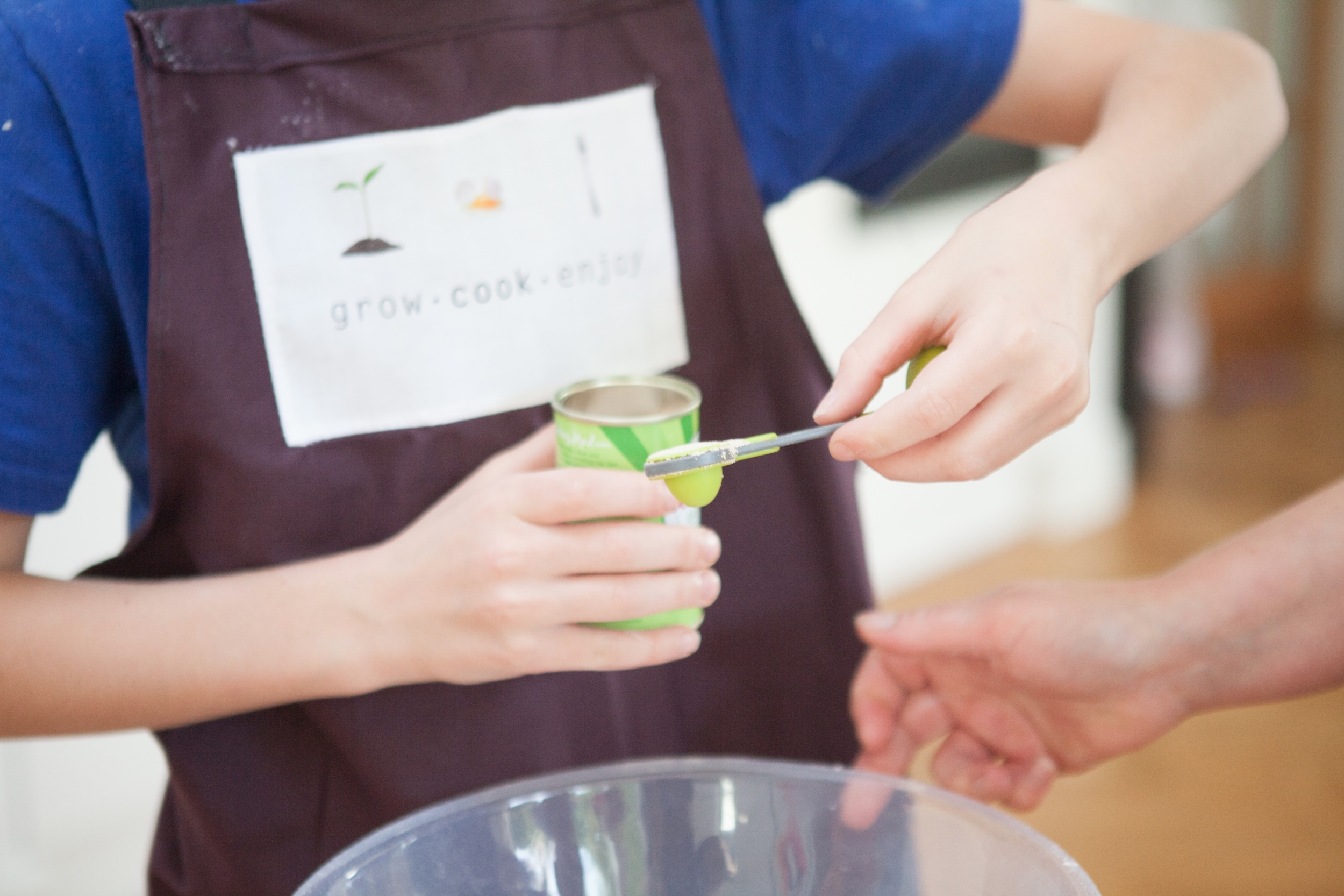 Child measuring yeast to add to a recipe