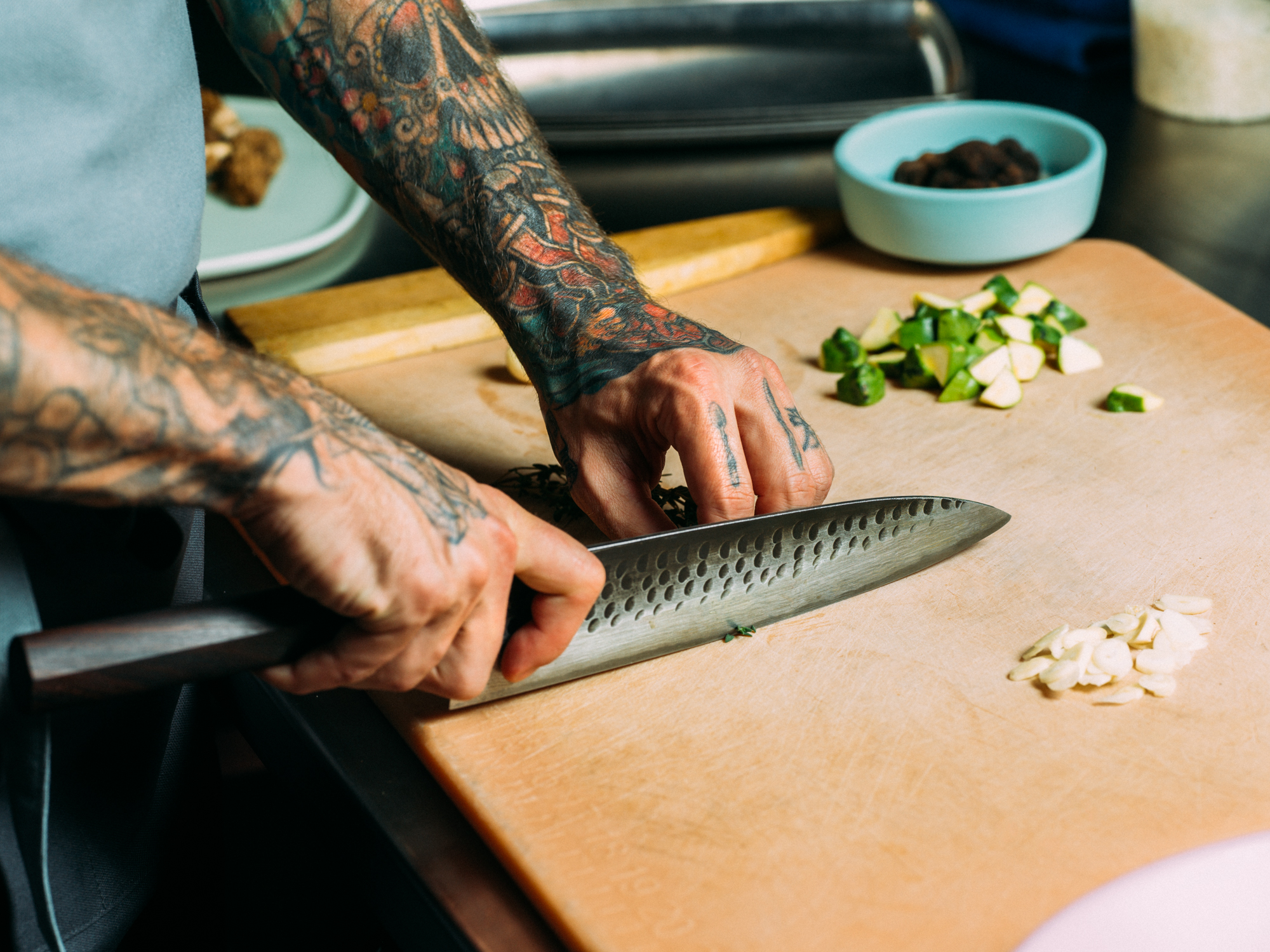 Tattooed arms holding a knife, slicing food ingredients on a cutting board.