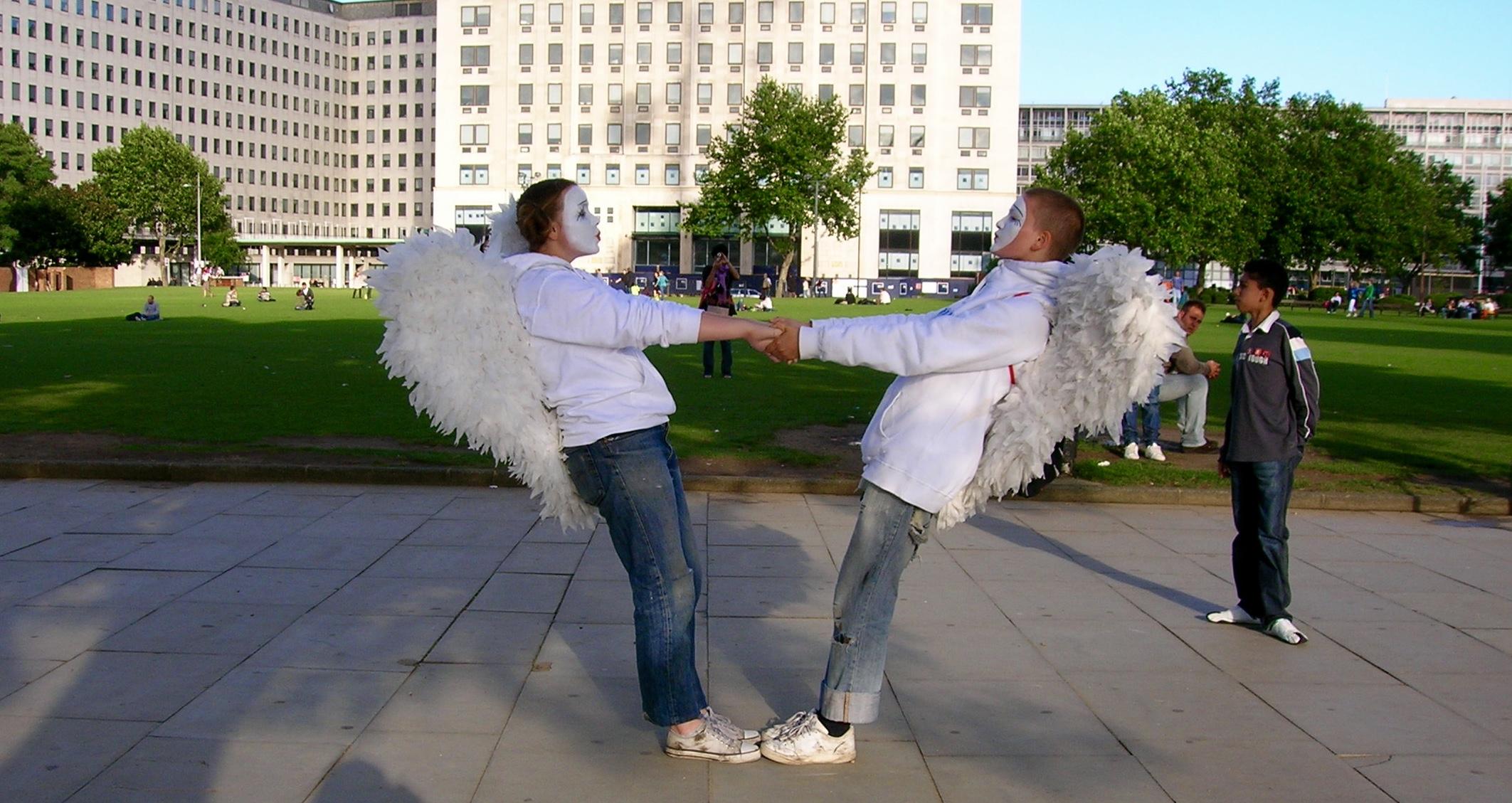 Dos mimos con alas y cara blancas agarrados de la mano en un parque