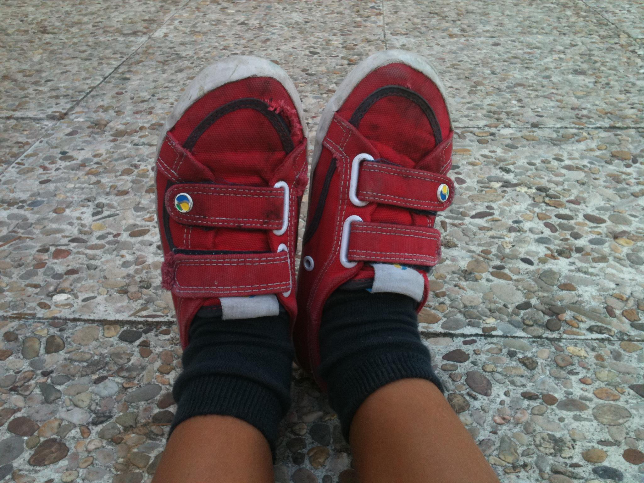 Dos pies juntos con zapatillas de deporte rojas