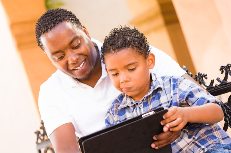 Father and son together on a tablet
