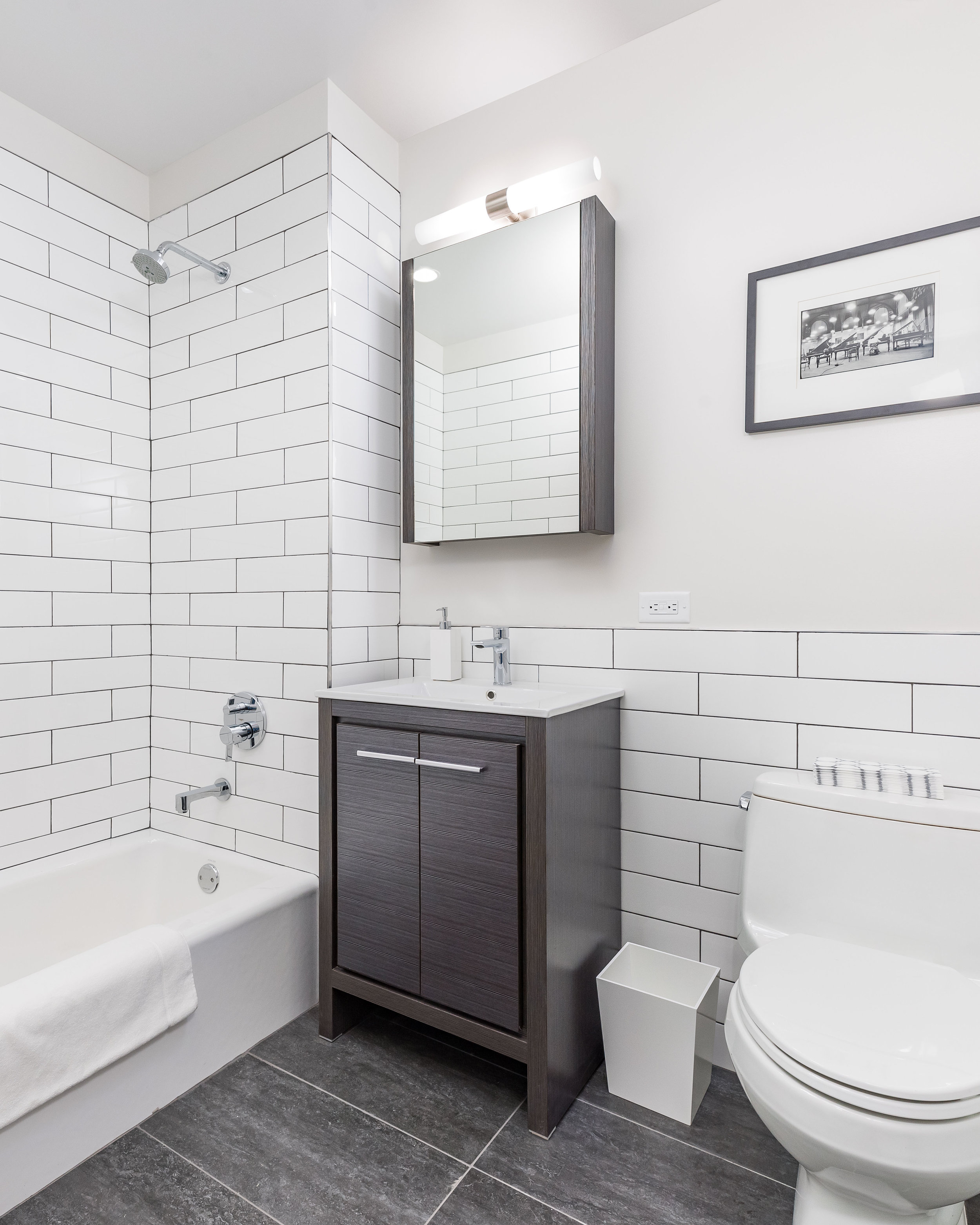 - Pamper yourself in the chic bathrooms, which feature best-in-class Hansgrohe fixtures, subway tiling and charcoal gray stone porcelain flooring.