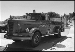 A 1953 Slinger fire truck is displayed outside the village's historic train depot.