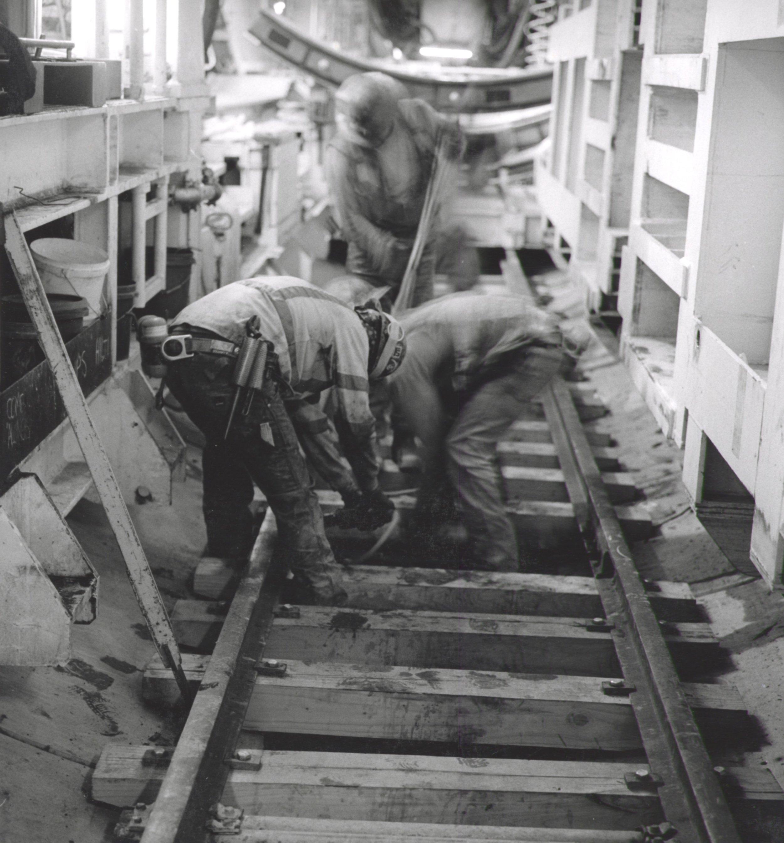 Miners Installing Rail Track Inside TBM