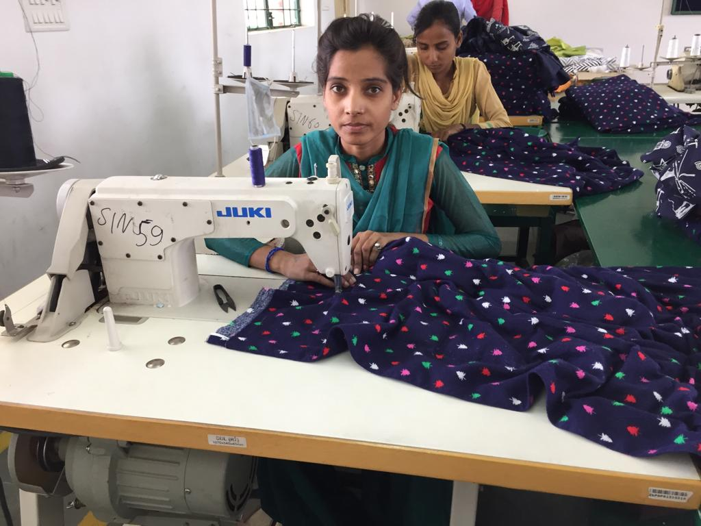 A young woman stitching together a weighted blanket at I Village.