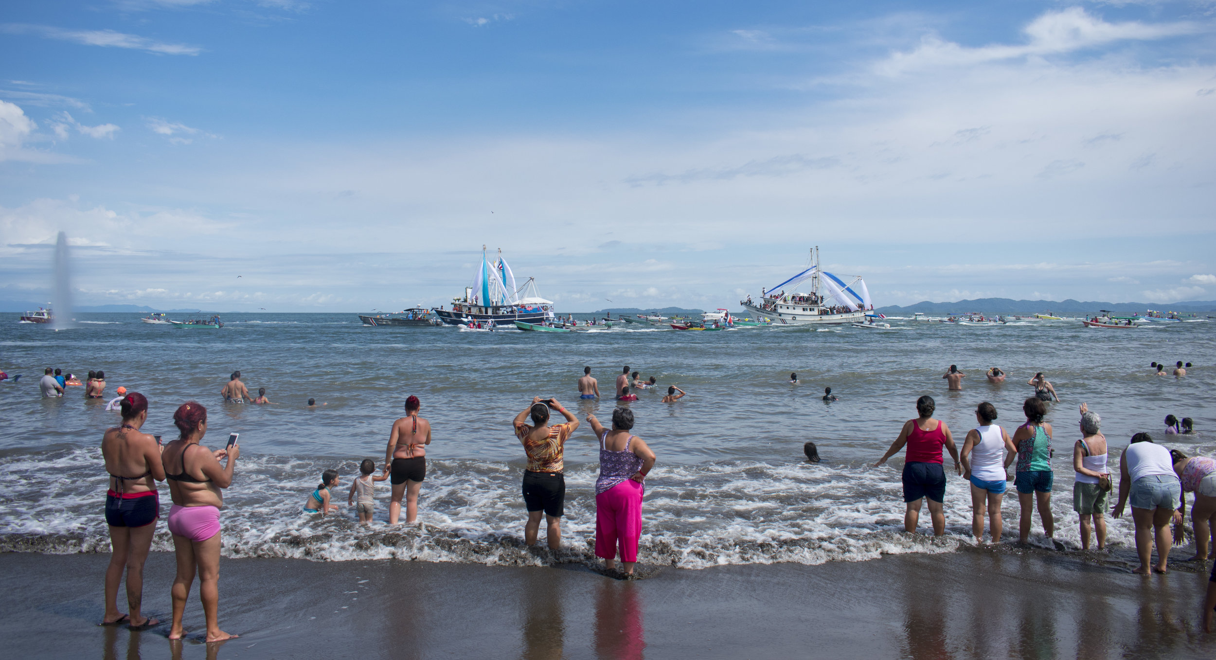 16. Onlookers watch the boat procession of the Virgen del Mar from the beach. The annual celebration is essential to the port town of Puntarenas as it is believed that she will bring protection and good luck to the fishermen.JPG