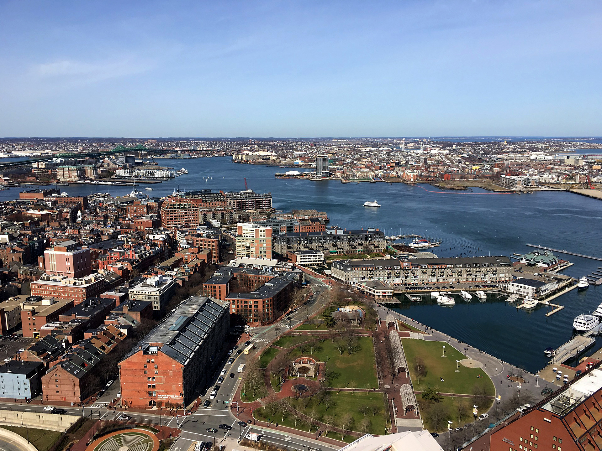 Recent view of Christopher Columbus Park from Custom House Tower, shows how some of the same Boston wharves and East Boston waterfront from the above early 20th-century photo look today. (NewtonCourt / wikimedia)