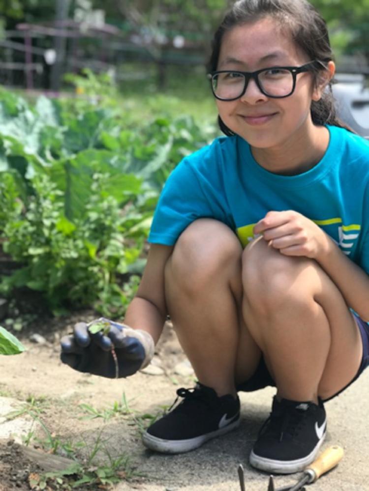 Ambassador Jessica helps weed the garden patch.