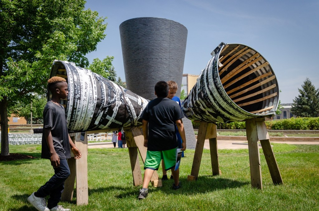 """CFUM youth with """"All Talk No Action,"""" their collaborative sculpture developed in response to Kerry James Marshall's """"A Monumental Journey (in the background)."""
