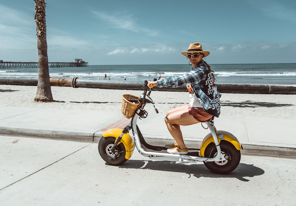 girl wearing a hat ride oside south on the strand yellow electric scooter.jpg