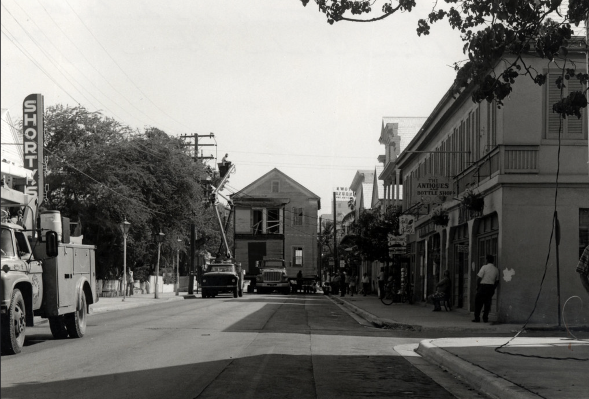 The 200 block of Duval Street with the house from 716 Fleming Street (where Library Garden now located) being moved to 115 Duval Street (Bagatelle Restaurant) in 1974. Photo from the Ida Woodward Barron Collection. Florida Keys Public Libraries.