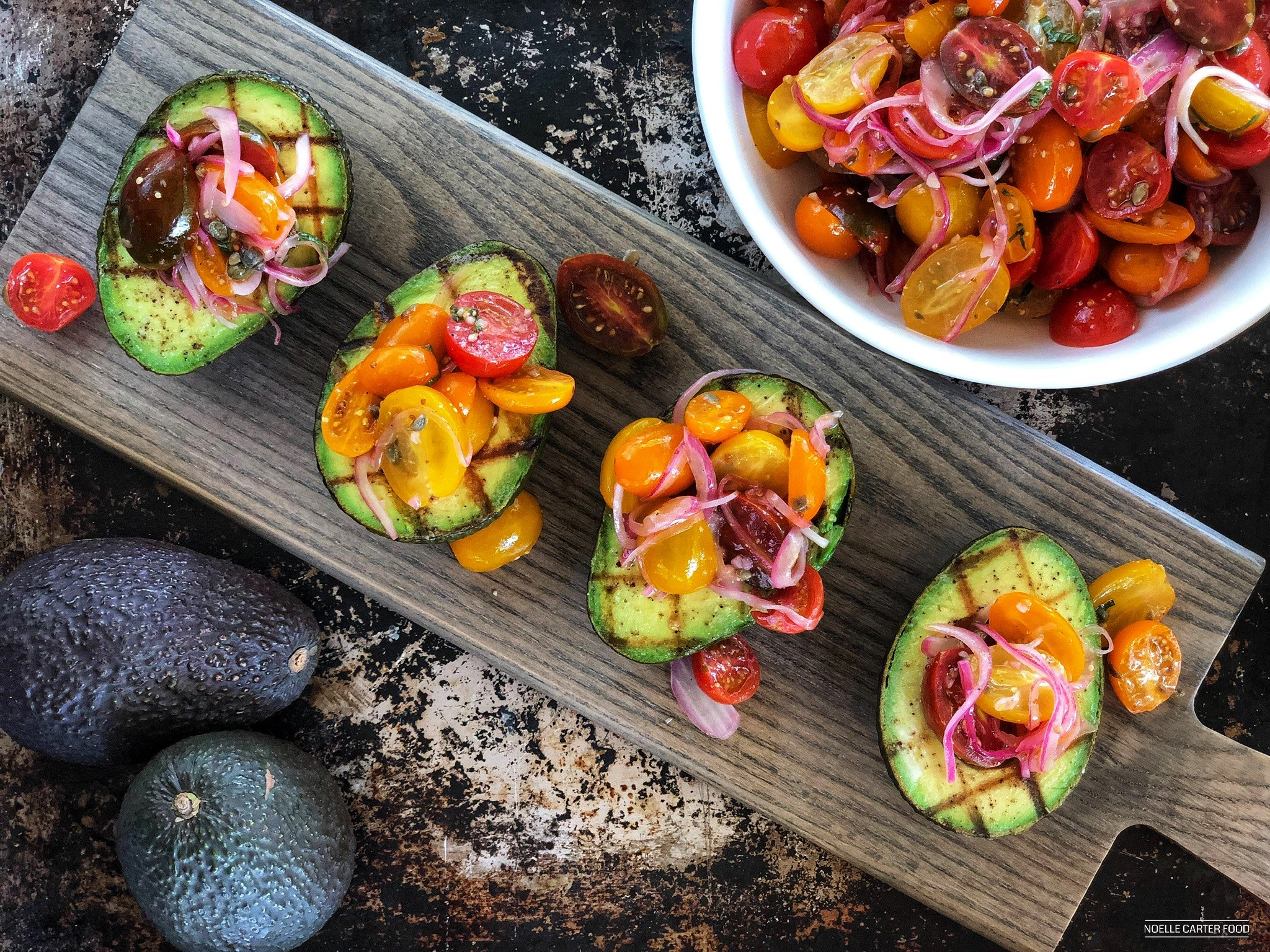 Grilled avocado with marinated tomato salad. (Noelle Carter)