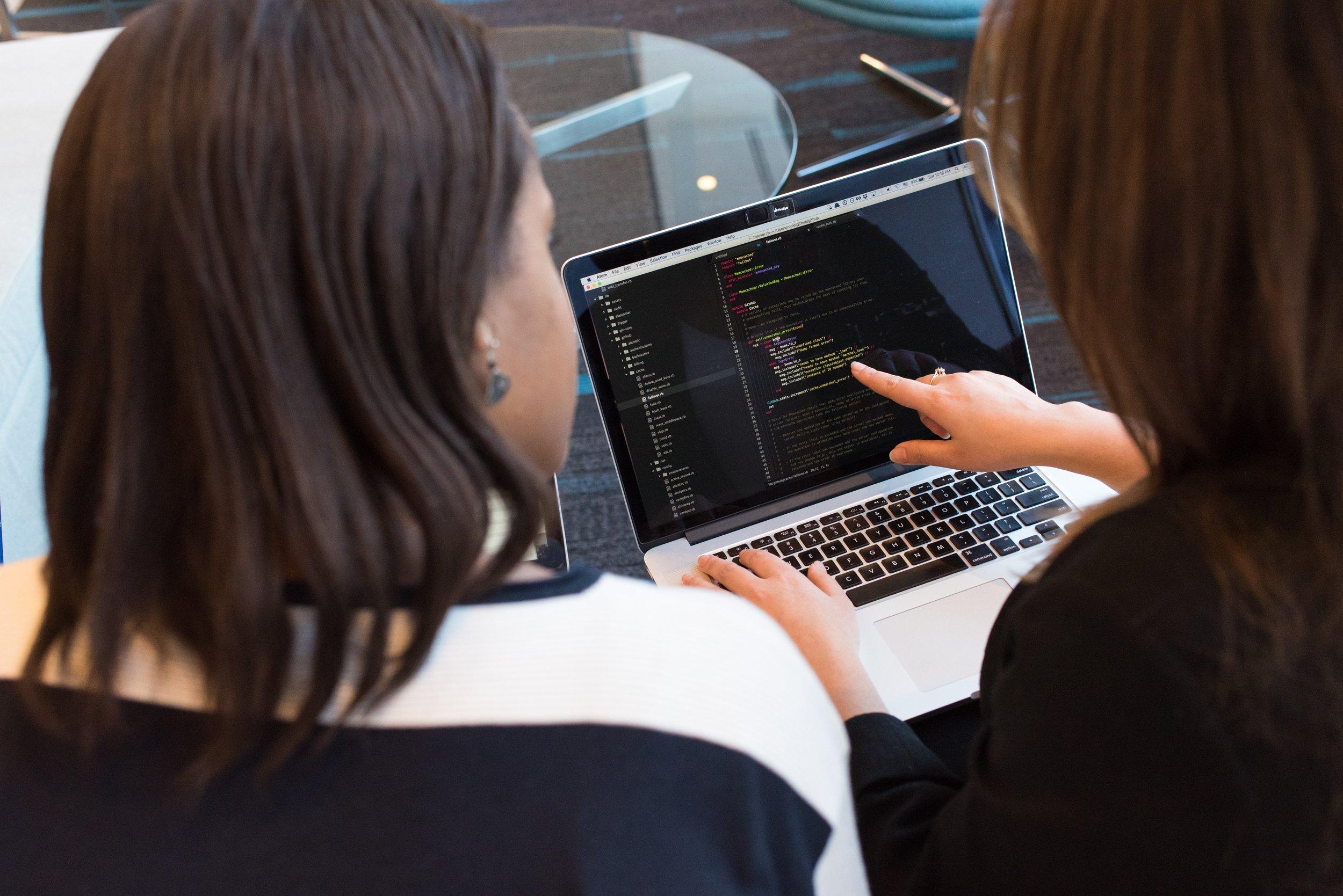 Ladies looking a code on computer