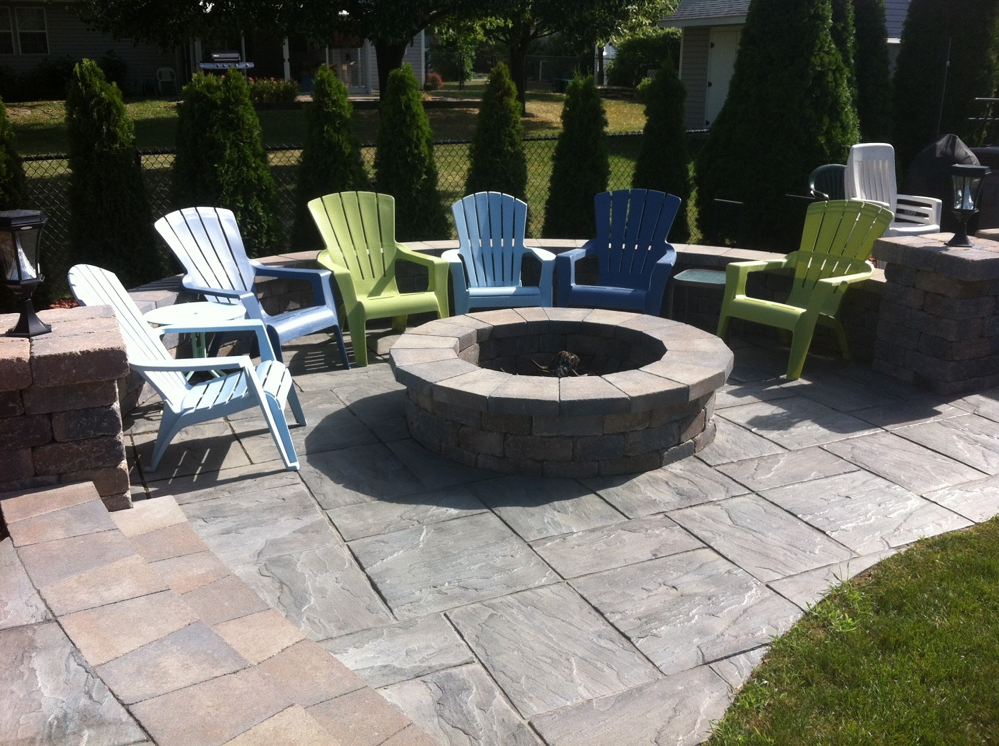 Brick patio with retaining wall and outdoor fireplace in Peotone, IL
