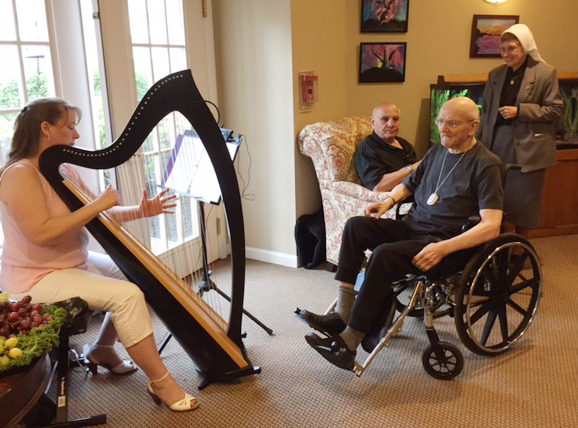 Father Berdis and Guests enjoy harpist Marcy Brown.jpg