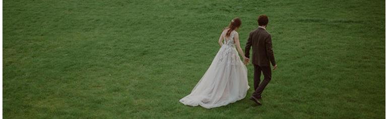 bride-groom-walking-grass.jpg