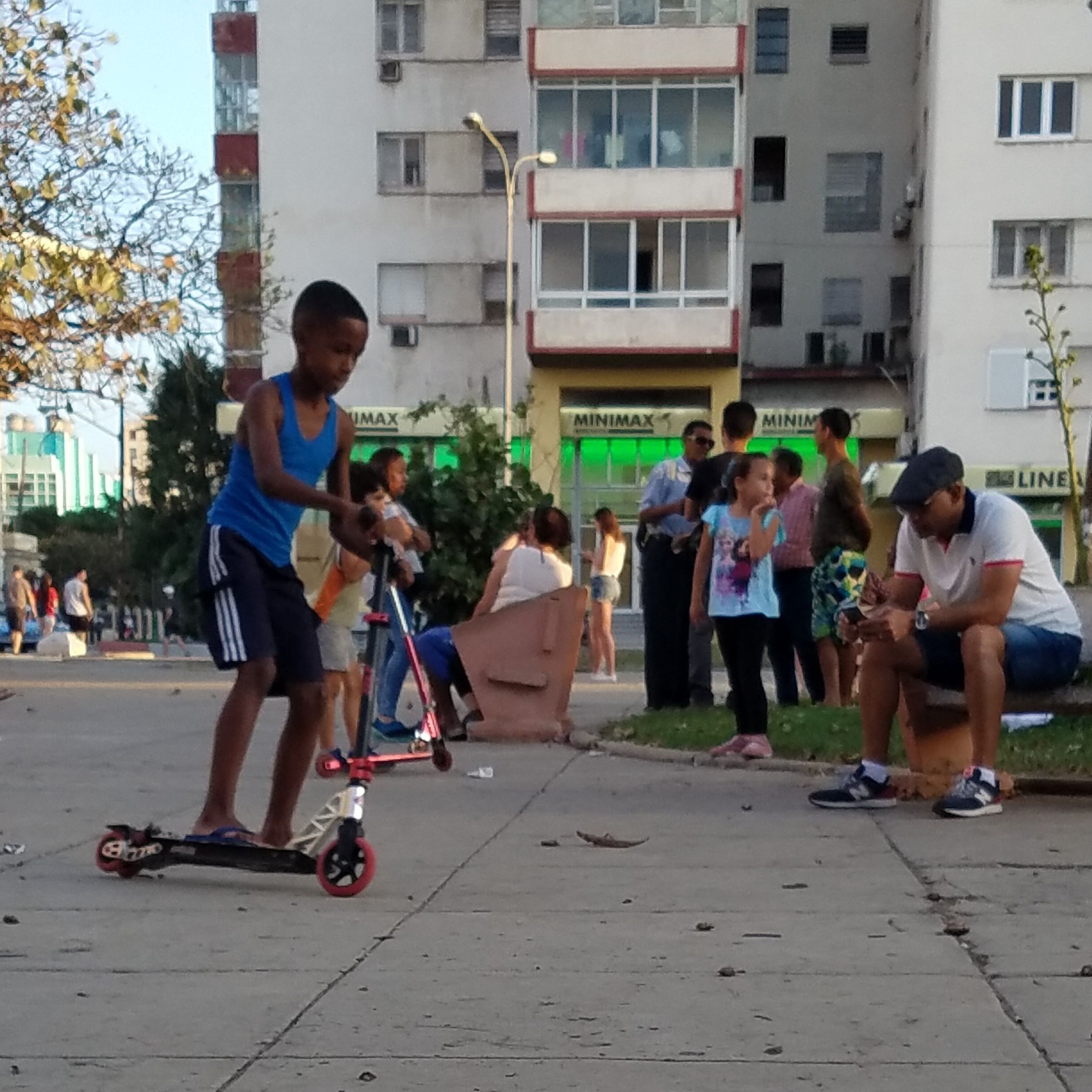 Kids playing at a WiFi park in the outskirts of Havana, Cuba. The adults are paying for the ilegal hourly WiFi so they can communicate with family members whom they haven't seen since they left Cuba.