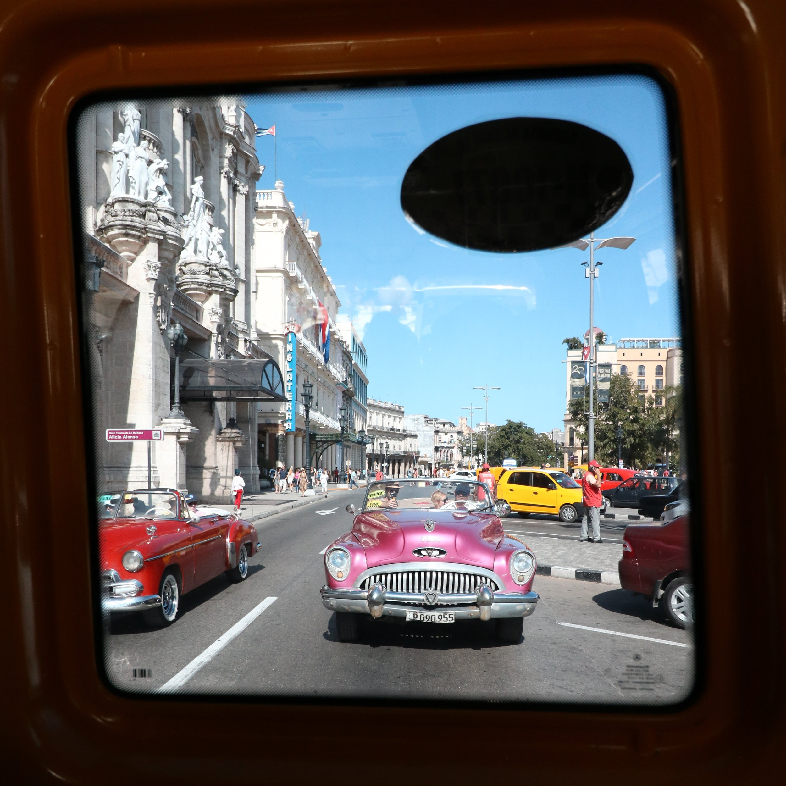 A classic American car filled with the Cuban driver and tourists.
