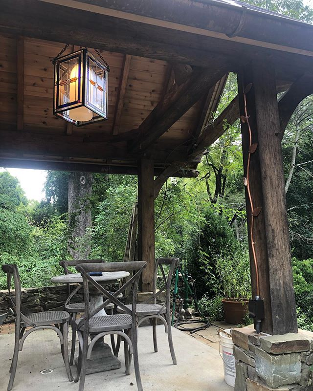 We had to get creative to hide the electric in this one. The owner had this slab put in and the electric run to this corner a couple years before we built the structure.  Thanks to: @shraderstoneco  @pclementsart  @littlepapercraneshop  For helping us get those details dialed in.  #garden #stonemasonry #quietspace #timberframe #copperroofing #collaborate #artwork #outbuilding #handblownglass #hardscapedesign #oakframedbuilding #lovewhatyoudo #keepcraftalive