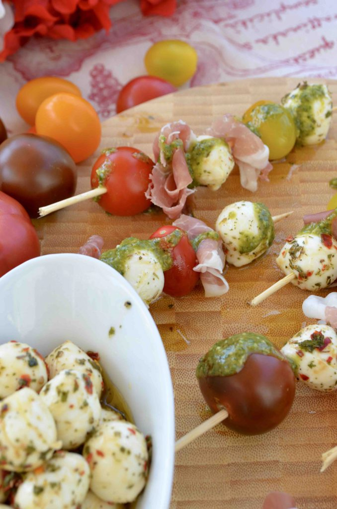 Caprese Skewers with Marinated Mozzarella, Tomatoes, Prosciutto, and Lemony Basil Pesto