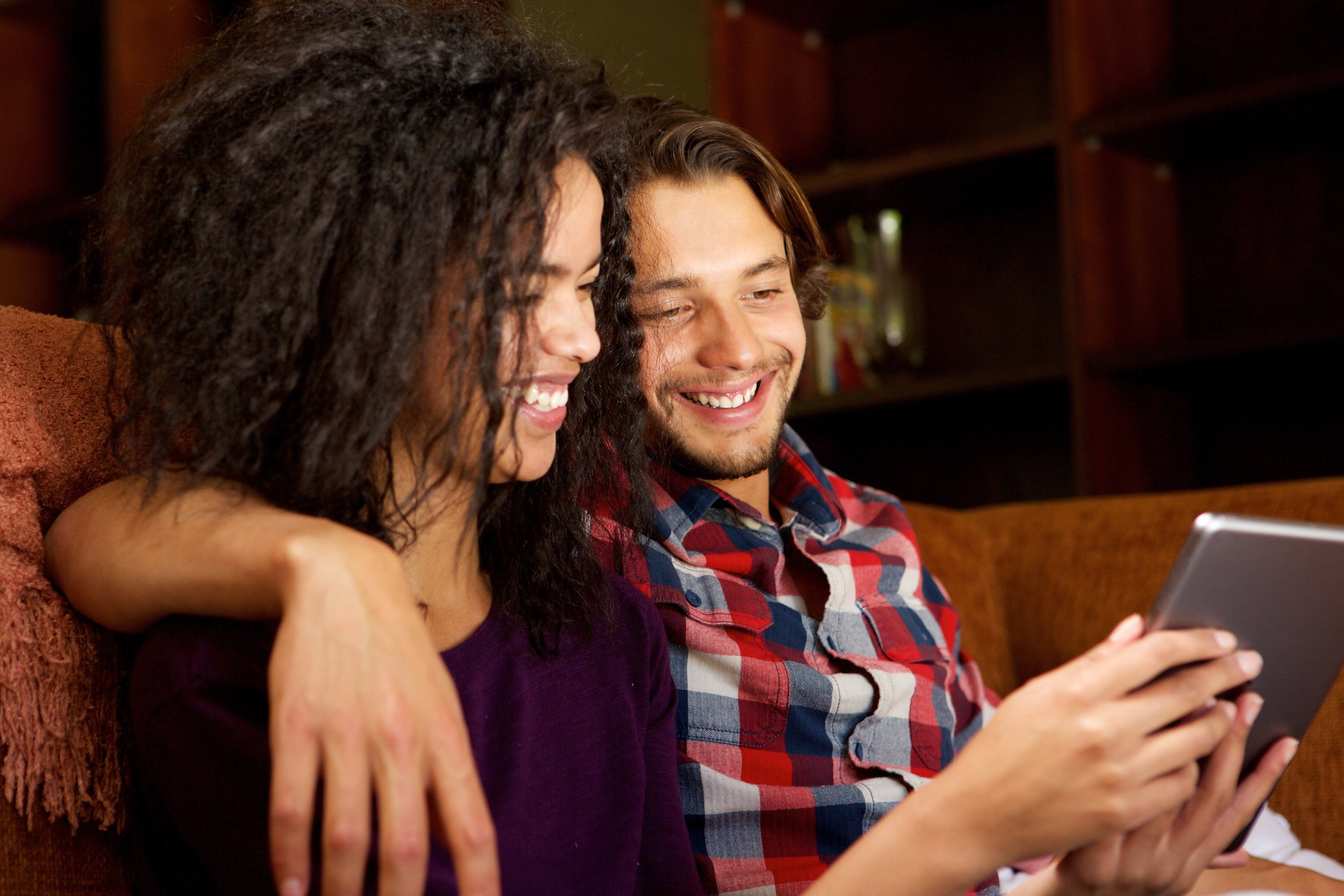 smiling biracial couple looking at tablet.jpg