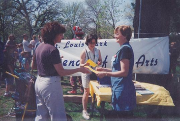 - Susan (right) spreading the Friends of the Arts mission at a summer arts festival in the early days of the organization.