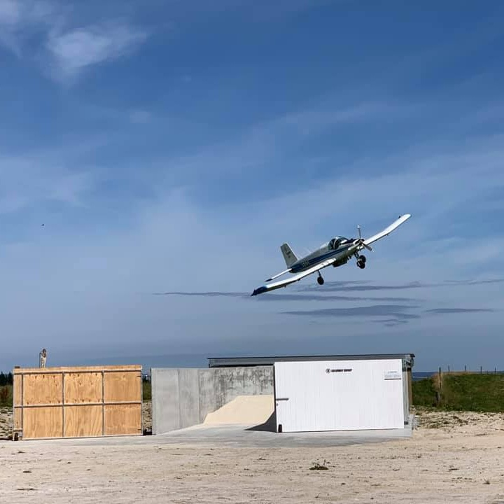 A plane flying over a Super Bin.
