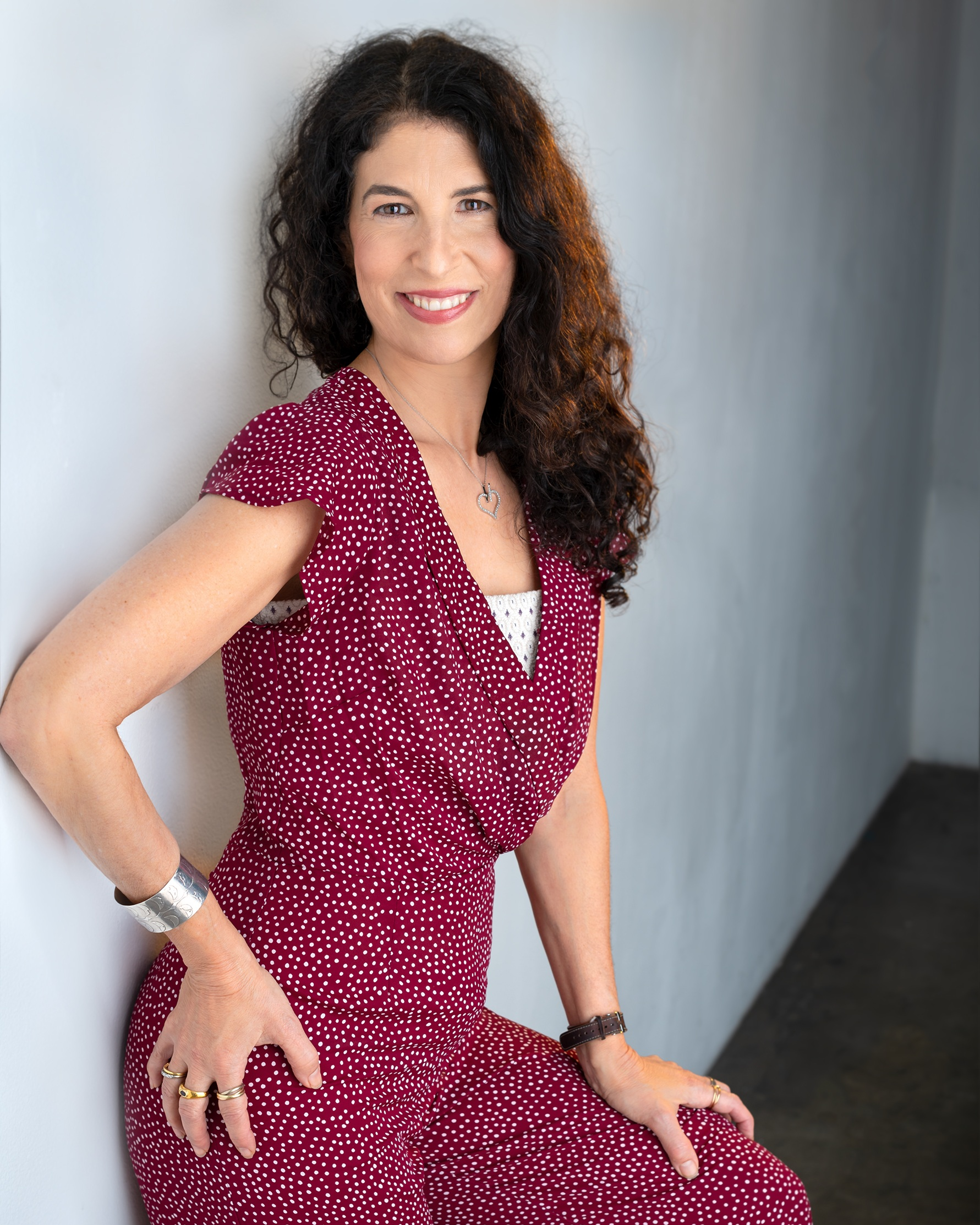 Denise Weisner, author and fertility expert, leaning up against a wall wearing a red jumper