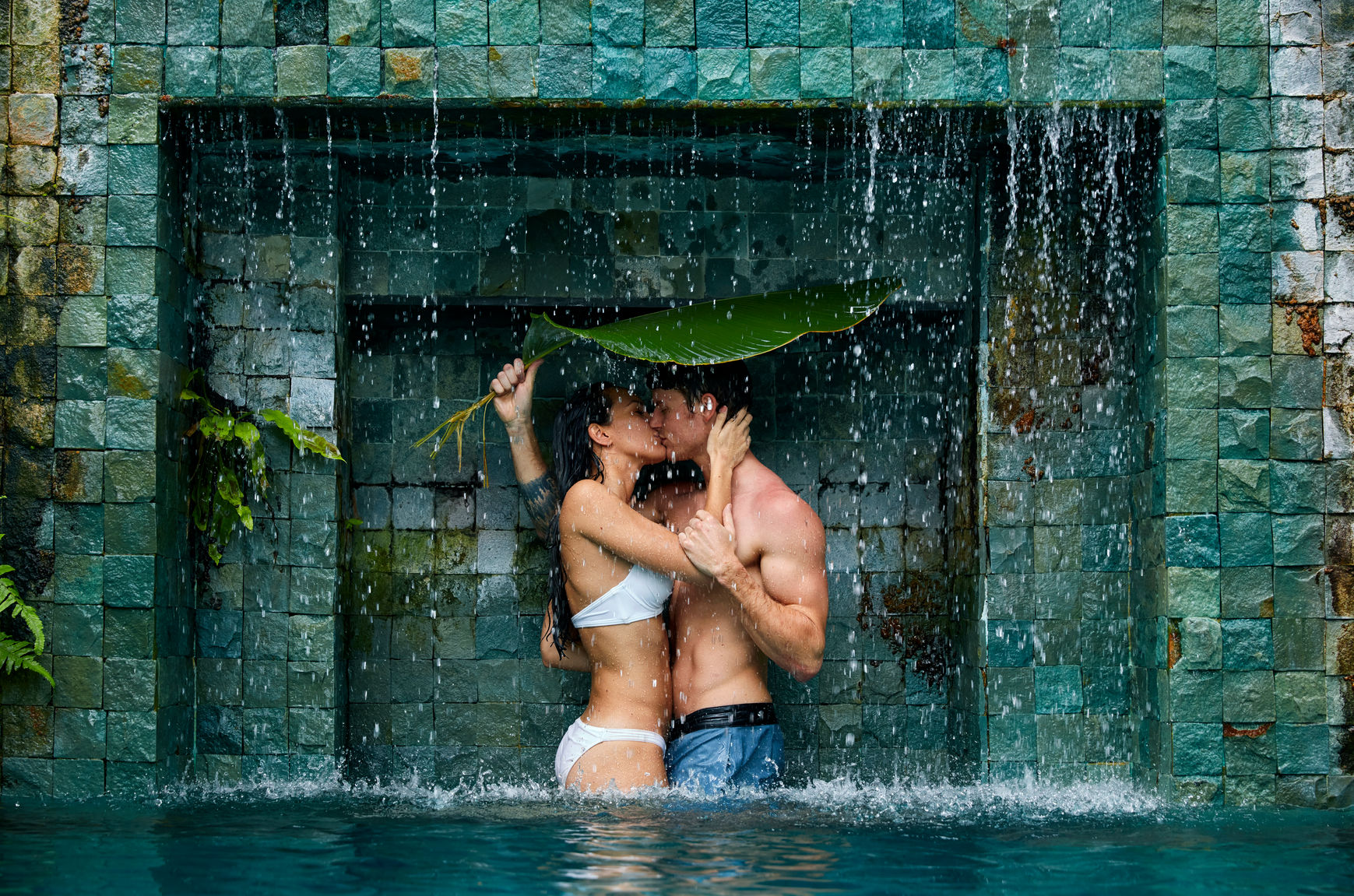 Sexy image of couple kissing in a pool under a waterfall. This is a couple who has reconnected through sex coaching.