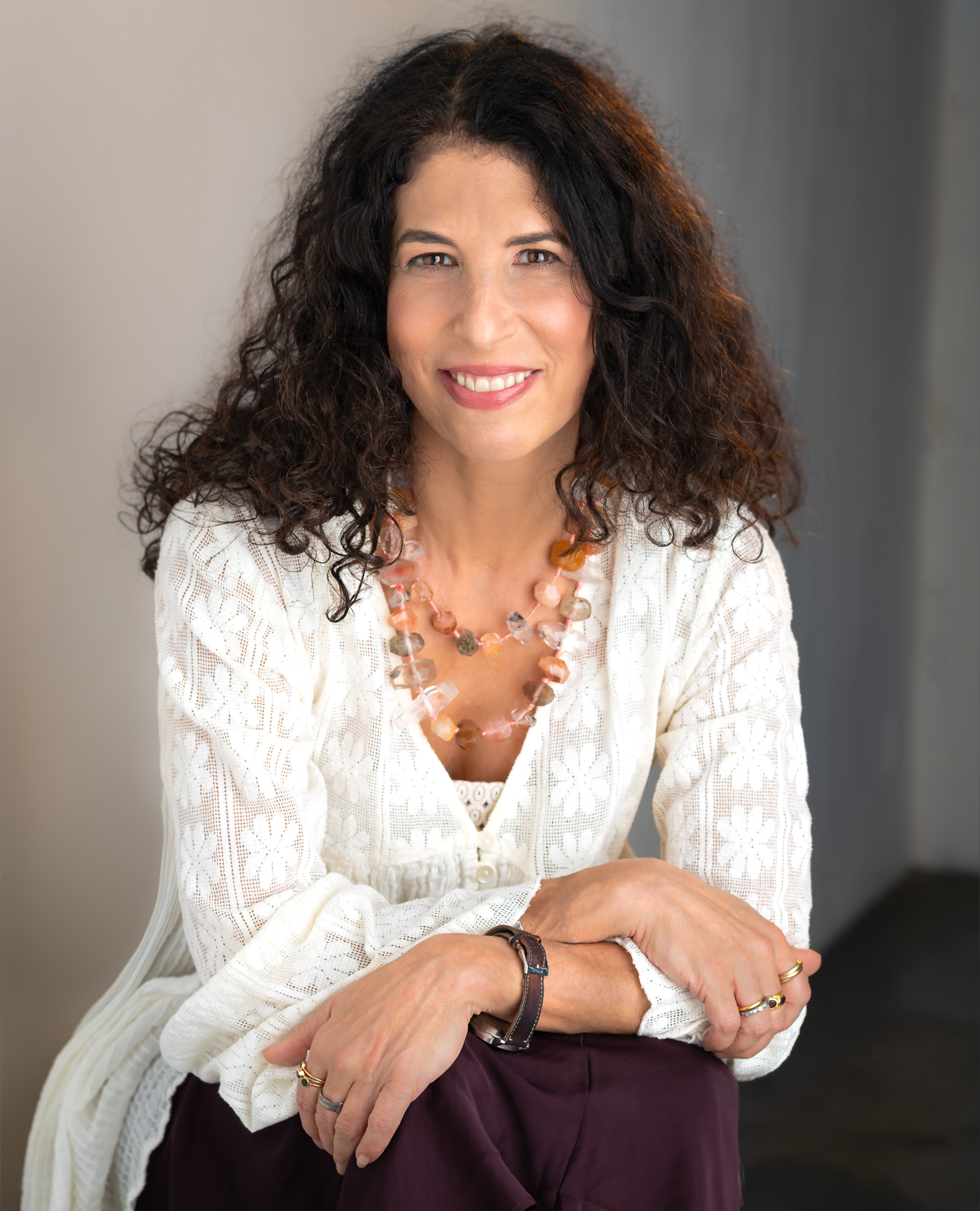 Denise Wiesner, Natural Fertility Expert and Author is leaning up against a chair wearing all white.