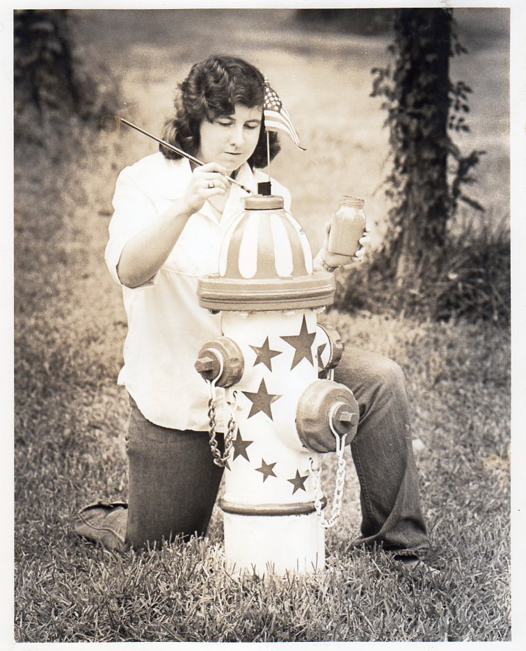 Timbergrove was draped in red, white, and blue in the summer of 1976, America's Bicentennial Celebration. to celebrate America's 200th birthday, homes, buildings, cars, and fire plugs were painted red, white, and blue. Here, Suzanne Daigle does her part by painting the fire hydrant at Wister and Shelterwood in section six, to ring in the patriotic spirit. PHOTO BY CHRIS DAIGLE