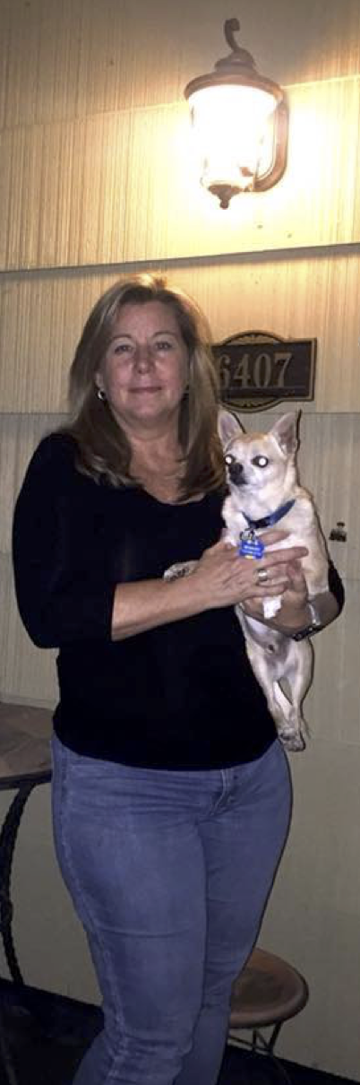 Security Committee member Annette Barry basks in the safe glow of her porch light with pup Henry.