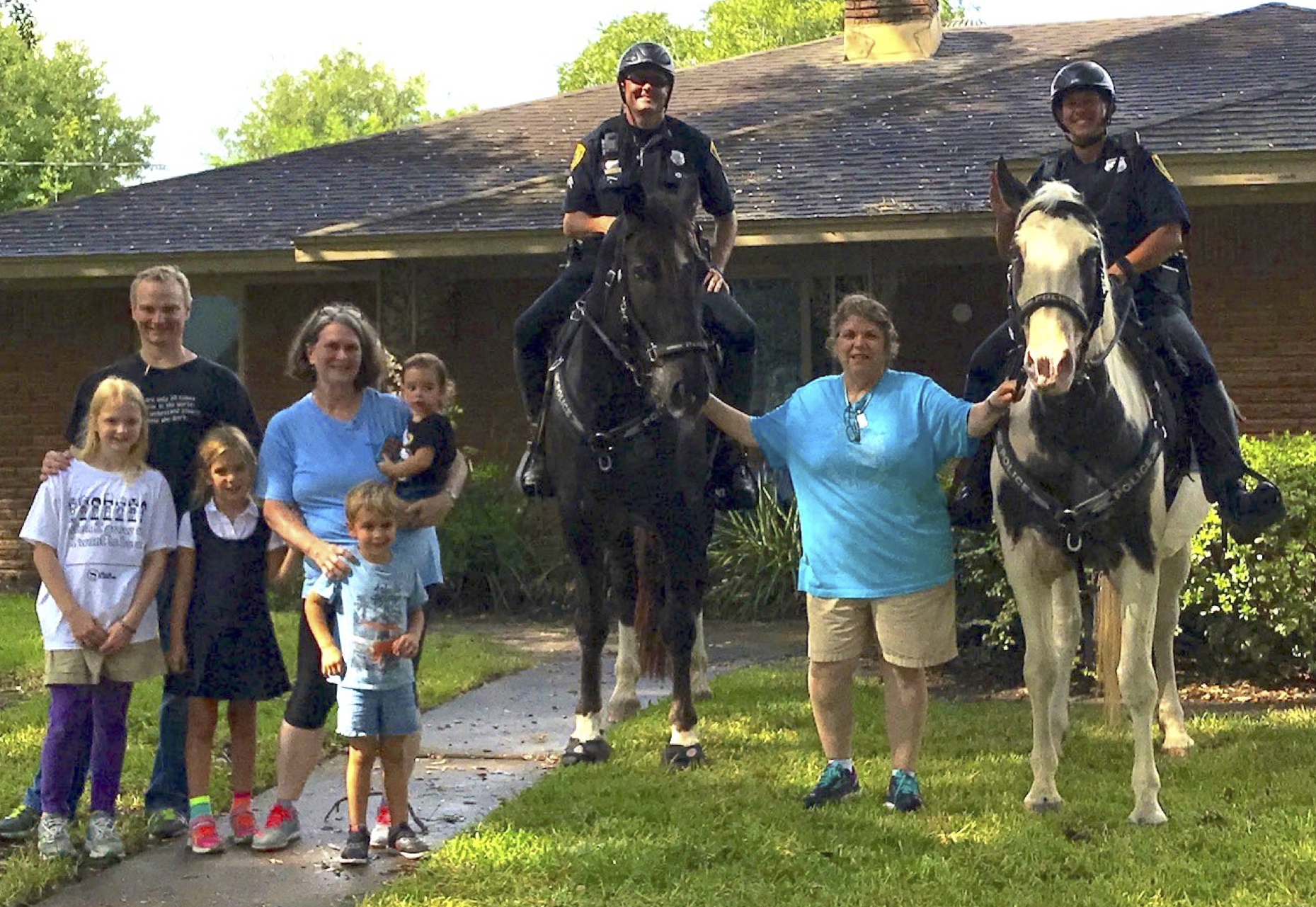 Ms Pat Woods with Officers Towler and Zboril, and (the real stars of the show) Texans Major and Star pose with neighborhood kids during an HPD mounted patrol visit to Timbergrove.