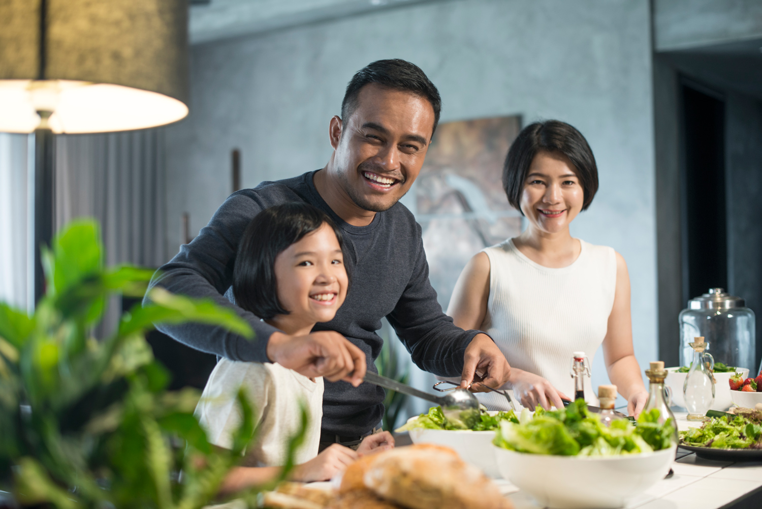Young-Asian-family-with-a-child-in-the-kitchen-preparing-healthy-meal.jpg