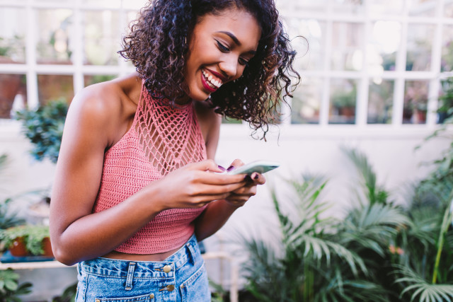 happy black girl phone pink tank top.jpg