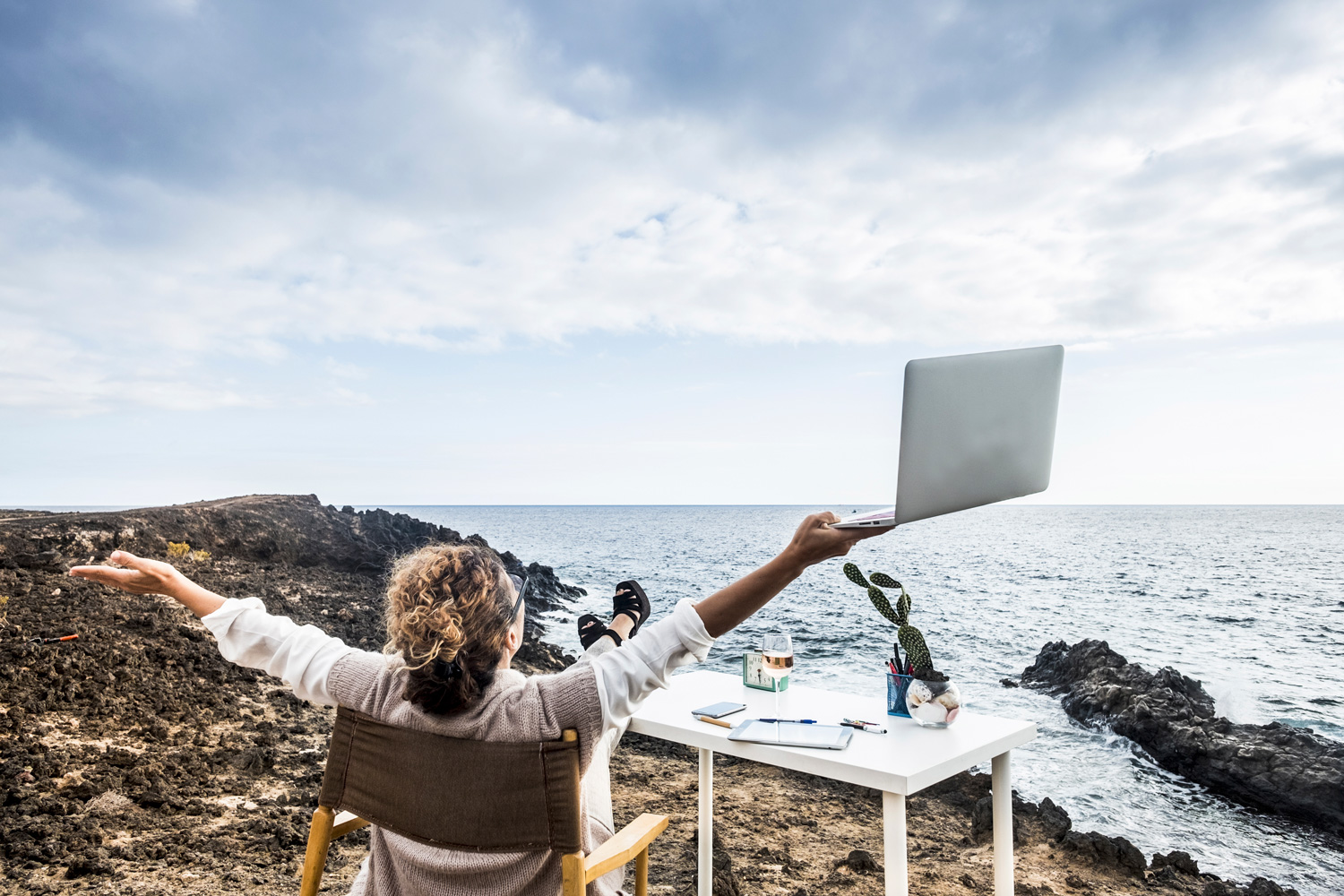 Woman-on-a-rocky-bitch-with-laptop-working-at-a-desk-freedom.jpg