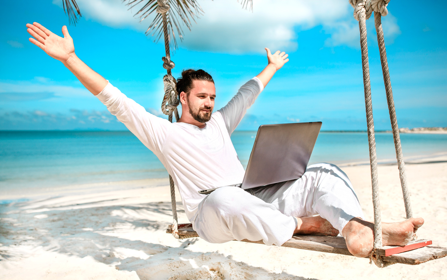 Location-independent-ocean-beach-paradise-man-sitting-on-a-swing-with-laptop.jpg