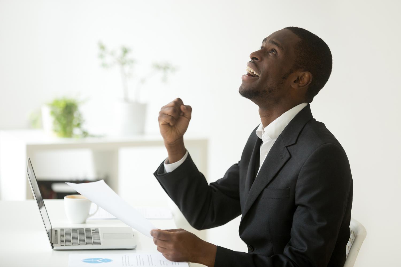 Grateful-man-wearing-suit-celebrating-sitting-in-front-of-laptop.jpg