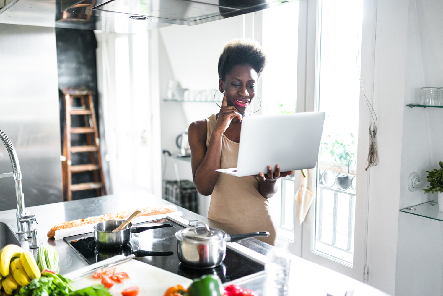 Black-lady-in-the-kitchen-with-laptop-cooking-fruits-vegetables-on-the-table.jpg