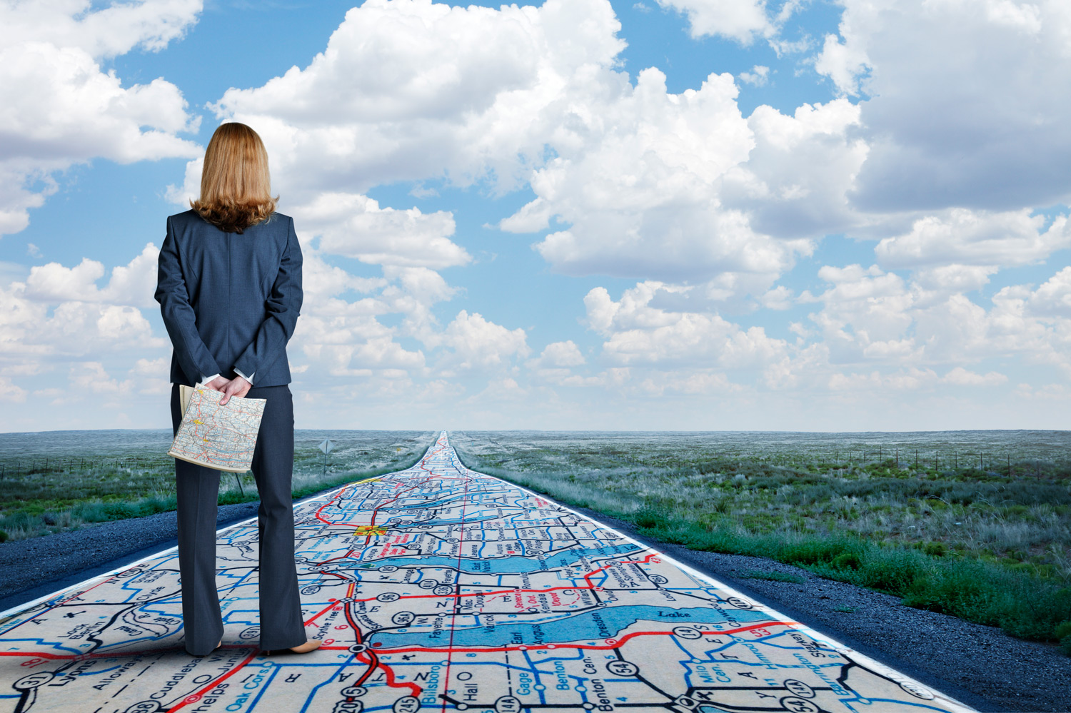 Businesswoman-Stands-On-Long-Road-With-Road-Map-Painted-On-It-614711200_5472x3644.jpg