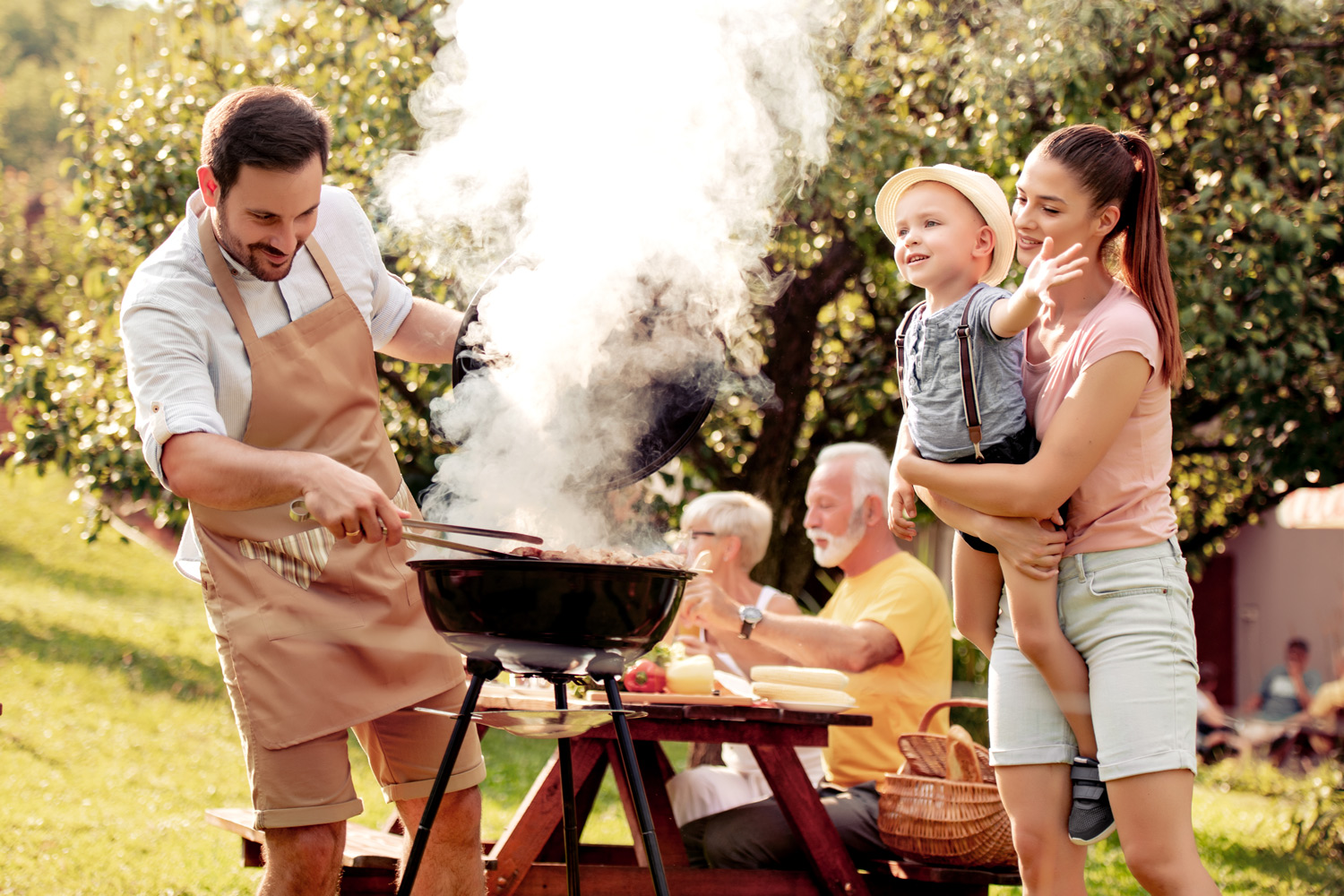 Happy-family-having-barbecue-in-the-garden-mom-dad-child-and-granparents-sunny-day.jpg
