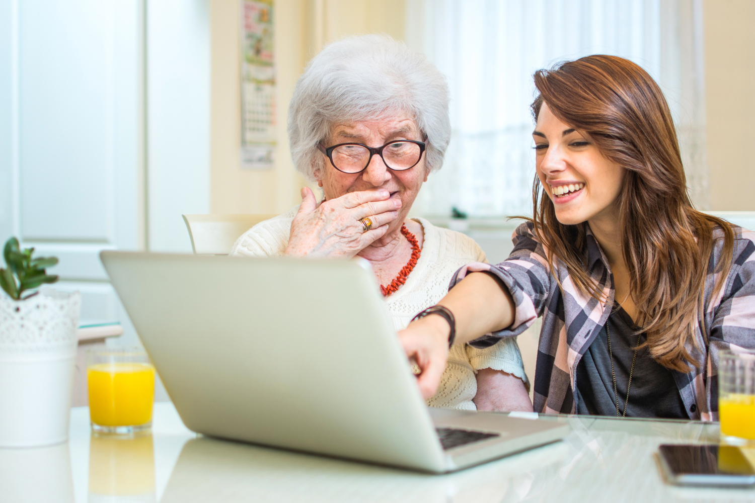 1-Granddaughter-pointing-at-something-on-laptop-screen-to-her-grandma-at-home.jpg
