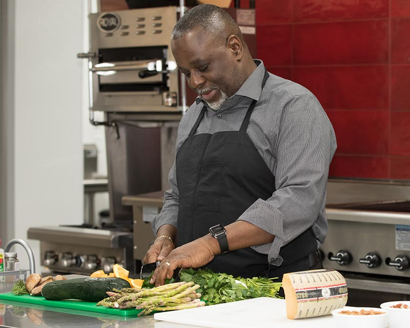 Culinary Director Dennis Briggs chopping vegetables in the Tribute kitchen