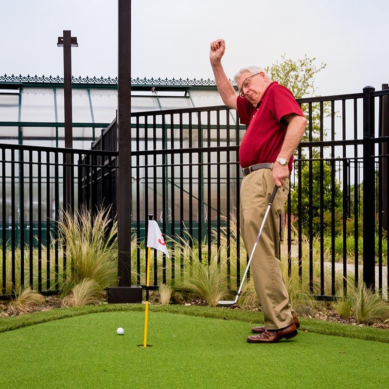 A man celebrates on a putting green