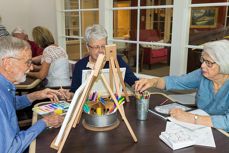 Seniors sitting together, creating art on easels